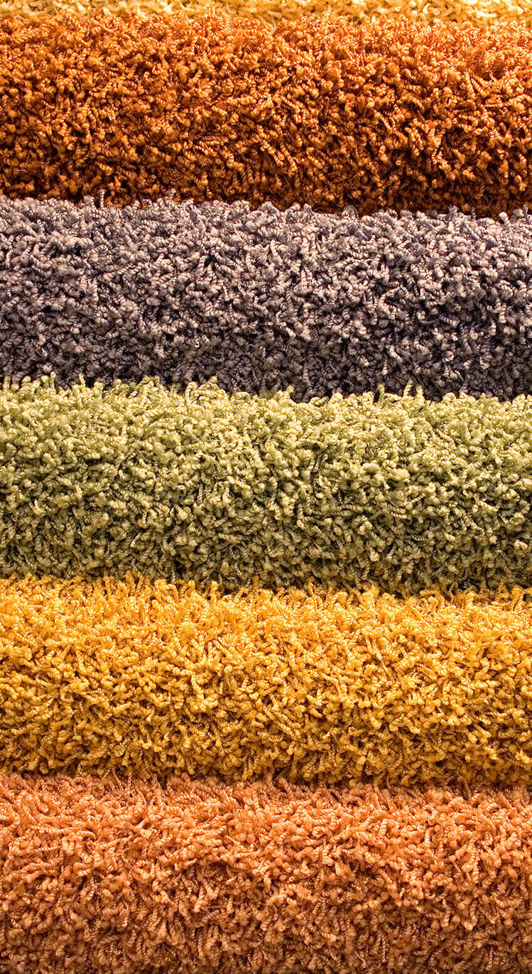 Photograph of 5 different colours of carpet: orange blue, green, yellow and pink