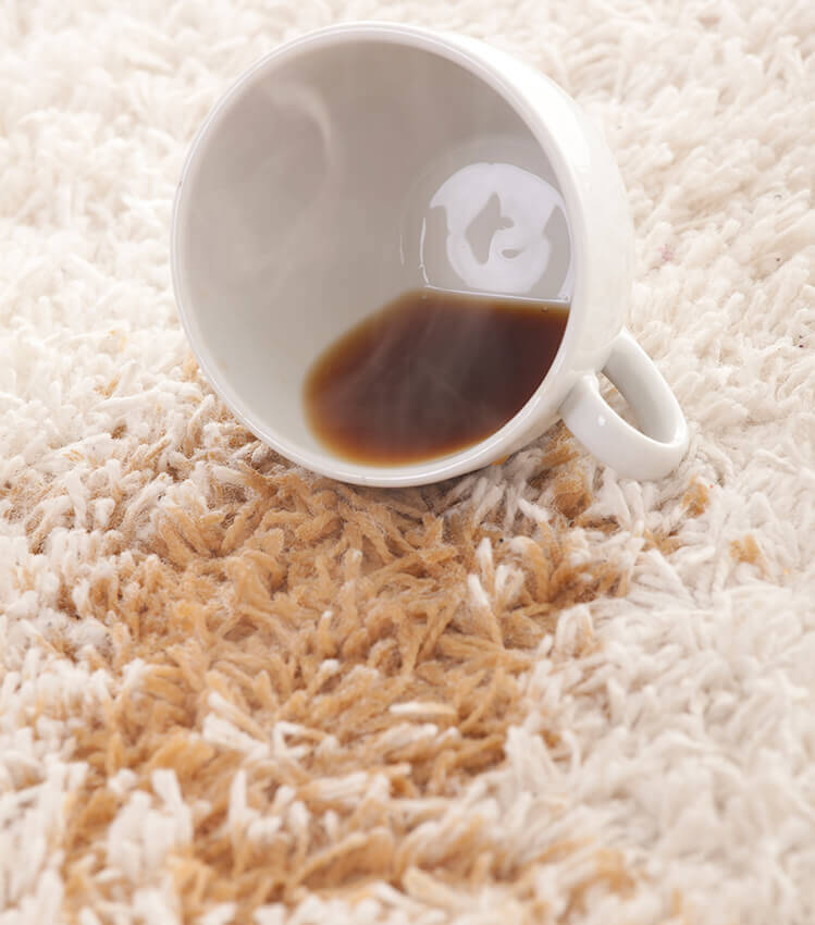 Photograph of a coffee cup spilling coffee onto a white carpet